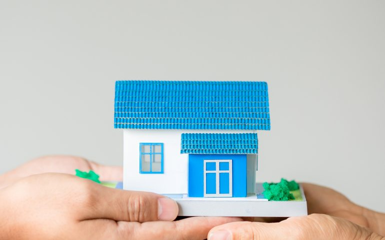 Real estate broker agent presenting and consult to customer to decision making sign insurance form agreement, home model, concerning mortgage loan offer for and house insurance.